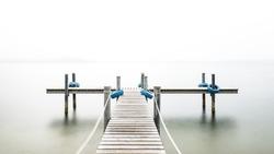 Wooden pier on the lake. Fog. Long exposure