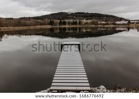 Wooden pier on the lake. Winter lake with pier and snow. Cloudy sky, lake with hills in background. View of the wooden pier. Winter countryside. Nobody. Perspective view of a wooden pier with snow