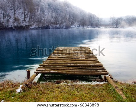 Wooden pier on the mountain river in winter morning