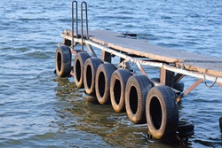 Wooden pier on the river close-up. On the side of the pier are old automobile tires. Old boat mooring on the river.