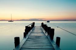 wooden pier on Tyrrhenian sea near Naples in summer morning