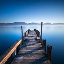 Wooden pier or jetty and lake at sunrise. Torre del Lago Puccini, Versilia, Massaciuccoli lake, Tuscany, Italy, Europe