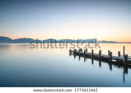 Photo of  Wooden pier or jetty and lake at sunrise. Torre del Lago Puccini, Versilia, Massaciuccoli lake, Tuscany, Italy, Europe