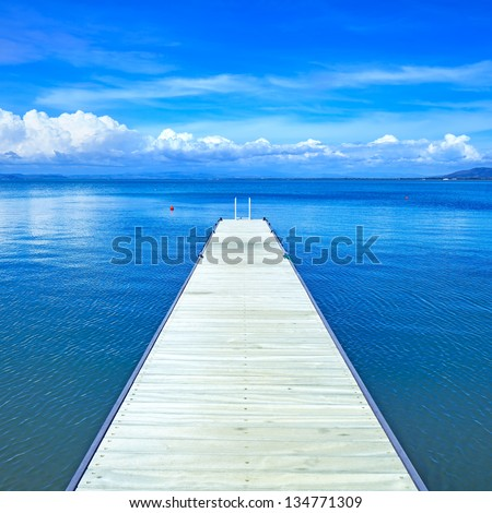 Wooden pier or jetty on a blue ocean and clear sky. Bay beach in Monte Argentario, Porto Santo Stefano, Tuscany, Italy