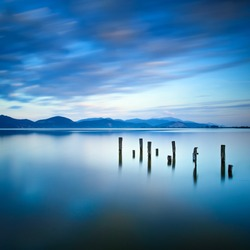 Wooden pier or jetty remains on a blue lake sunset and cloudy sky reflection on water. Long exposure, Versilia Massaciuccoli Lake, Tuscany, Italy.