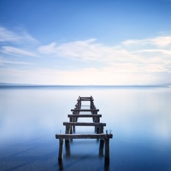 Wooden pier or jetty remains on a blue lake sunset. Long Exposure photography