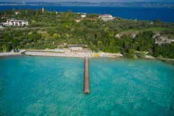 Wooden pier, turquoise water. Panoramic aerial view of Lido delle Bionde beach, Sirmione, Lake Garda, Italy. Island against the blue sky