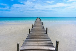 Wooden pier with blue sea and blue sky background