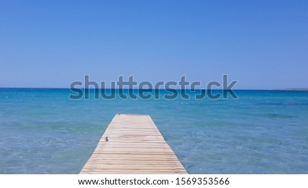 Wooden pier with blue sea and blue sky on background. Wooden bridge on the beach to the sea in the blue sky. Wooden bridge on the beach and blue sky in summer. stock photo