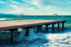 Wooden pier with metal ladders, splashing waves and the sea on a windy summer day.