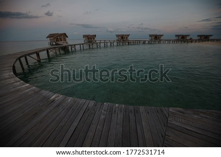Wooden pier with overwater wooden bungalows. Overwater villas on the tropical lagoon, tropical islands, sunset time stock photo
