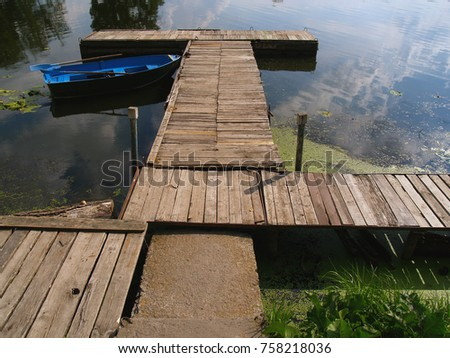 Wooden piers of the pier on the pond and the blue old boat on the surface of the water. #758218036