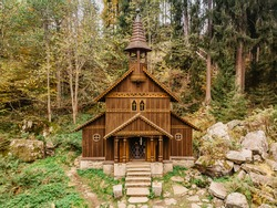 Wooden pilgrimage rural Chapel of Virgin Mary (CZ: Stozecka kaple) and iron cross standing in forest at the altitude of 950 m, Czech Republic,Sumava National Park.Folk wood carving.Rural architecture