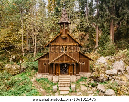 Wooden pilgrimage rural Chapel of Virgin Mary (CZ: Stozecka kaple) and iron cross standing in forest at the altitude of 950 m, Czech Republic,Sumava National Park.Folk wood carving.Rural architecture Foto stock ©