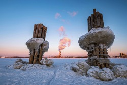 Wooden pillars with blocks of ice stick out from under the ice of a frozen river against the backdrop of a blue sky at sunset. Winter calm landscape