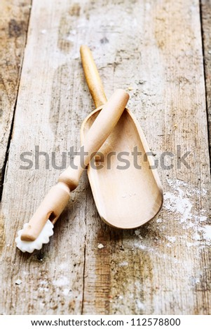 Wooden pizza cutter and flour shovel with remnants of flour in a rustic kitchen on an old grainy textured wood surface