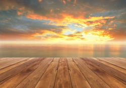 wooden plank and beautiful sunrise in the sea