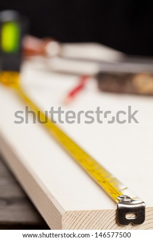Wooden plank with measurement tape and tools with selective focus