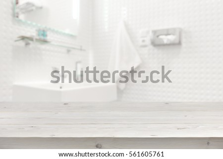 Wooden planks surface and blurred bathroom interior as background.