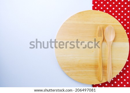 Wooden plate, tablecloth, spoon, fork on table background