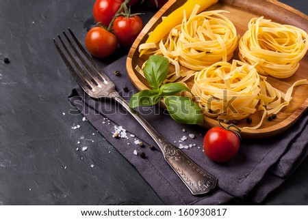 Wooden plate with dry pasta, fresh tomato, basil and yellow chili pepper served with sea salt and vintage fork on dark gray background