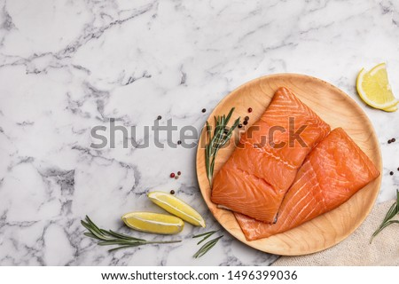 Wooden plate with tasty salmon fillet on marble table, flat lay. Space for text