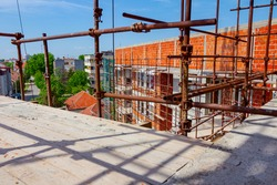 Wooden platform above building site as a part of scaffold placed against edifice under construction for logistics need.