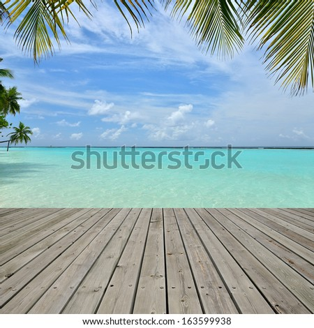 Wooden platform beside tropical beach with palm tree leaf