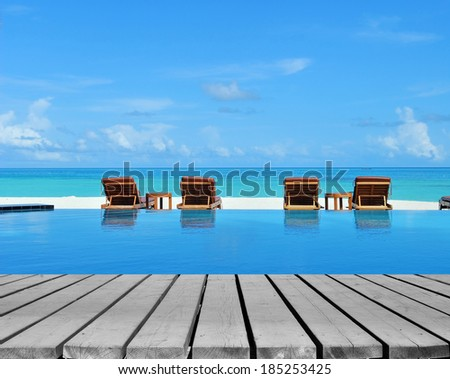 Wooden platform beside tropical resorts swimming pool