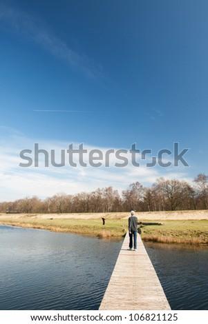 Wooden platforms in nature water lake with walking man