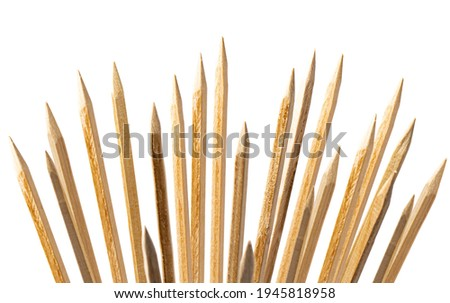 Wooden pointy stakes stick out in different directions on white. Stockfoto ©