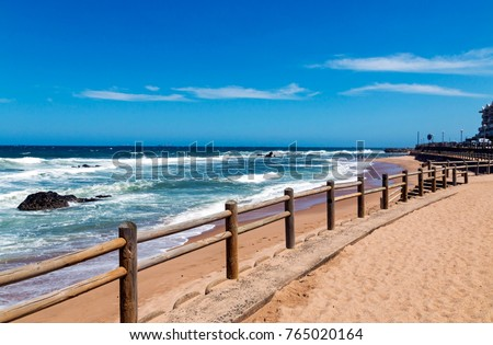Wooden pole barrier on beachfront against beach sea and blue sky landscape at Mdloti in Durban, South Africa #765020164