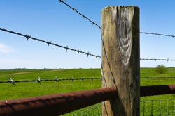 Wooden post and barbed wire with prairie and blue skies in the background.