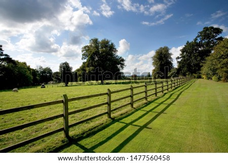 Wooden post and rail fencing around a tidy empty paddock