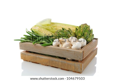 Wooden Produce crate with assorted vegetables, over a white background with reflection. Items include, corn on the cob, green beans, artichokes, and mushrooms.