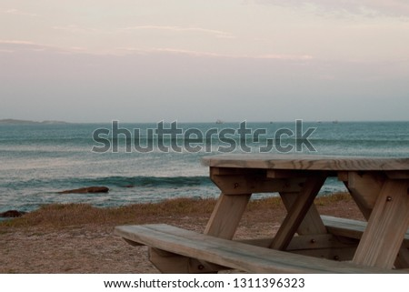 Wooden public picnic table overlooking the South African ocean; almost sunset, pink light