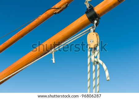 Wooden pulley with ropes, blue sky on background.