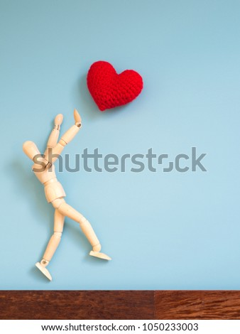 Wooden puppet jumping from the wooden floor in the air to catch the red heart floating in the sky. Wooden puppet try to jump to catch love. Concept of effort and love #1050233003