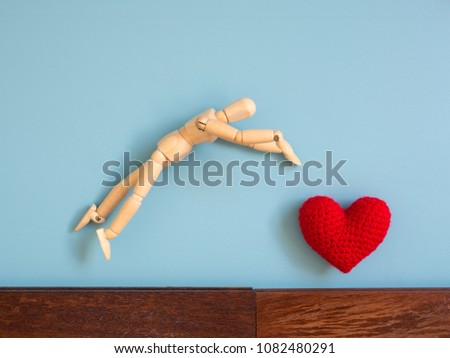 Wooden puppet jumping from the wooden floor in the air to catch the red heart floating in the sky. Wooden puppet try to jump to catch love. Concept of effort and love #1082480291