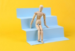 Wooden puppet on stairs podium, yellow background. Concept art, minimalism