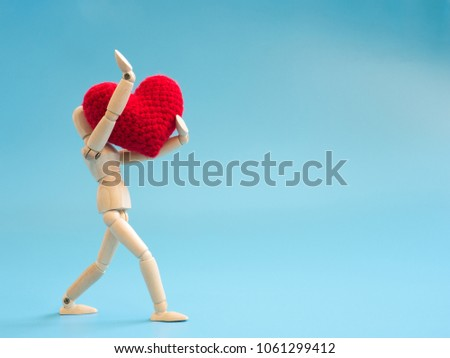 Wooden puppet walking and hold red heart on the sky blue screen background. Wooden puppet handle the heart with love and care. Concept of take care and love.
