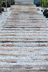 Wooden Railway sleepers between fine gravel flooring outdoor perspective shot overcast day