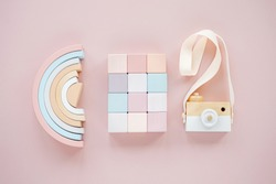 Wooden rainbow, colorful blocks and toy camera. Stylish baby toys on pastel pink background. Eco friendly, plastic free toys accessories for kids. Flat lay, top view