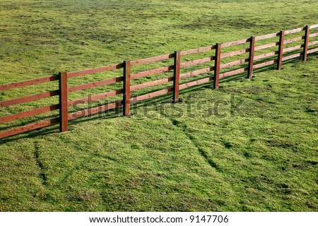 Wooden ranch style fence in a grass field.