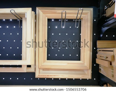 wooden rectangular picture frames on a metal hook on the showcase. accessories for artists. making pictures. handmade products made of wood.