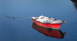 wooden red boat on the water of a small port in Portugal
