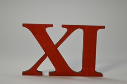 Wooden red roman numeral eleven on a white background