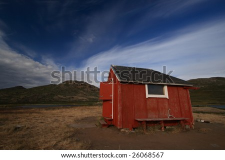 Wooden red shelter hut in the mountains in Greenland