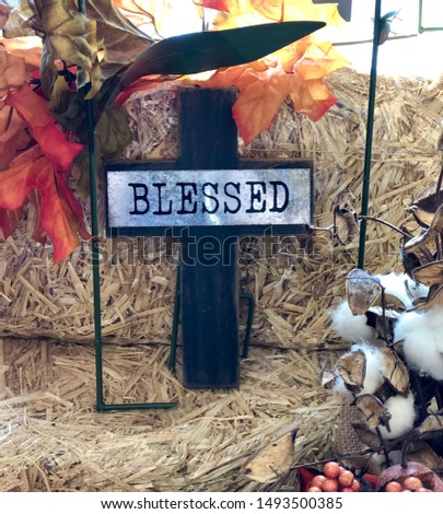 Wooden religious cross with the word blessed with hay and fall themed colors in the background