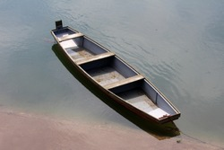 Wooden river boat made of dilapidated wooden boards with grey metal parts tied to concrete river bank with strong rusted chain surrounded with calm water